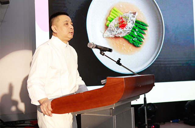 (The Good Food's chef Zhang Shao Gang introduce the dish Sea Bass steamed with rice wine with a side of asparagus.)